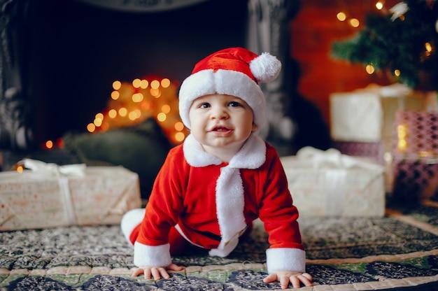 Cutte petit garçon à la maison près de décorations de noël Photo gratuit