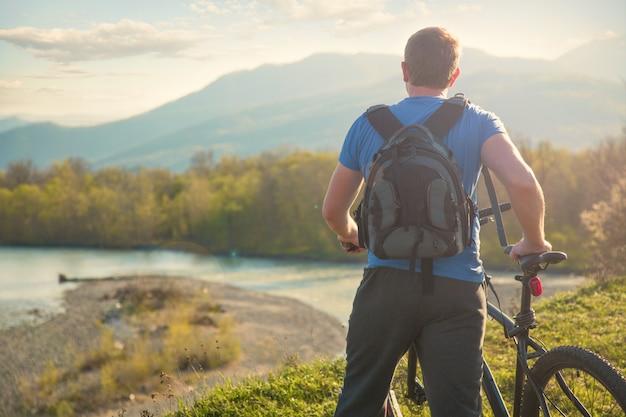 Cycliste garçon debout sur une montagne et regarde la rivière au coucher du soleil Photo Premium