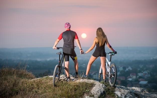Cycliste romantique avec des vélos de montagne debout au sommet d'une colline Photo Premium