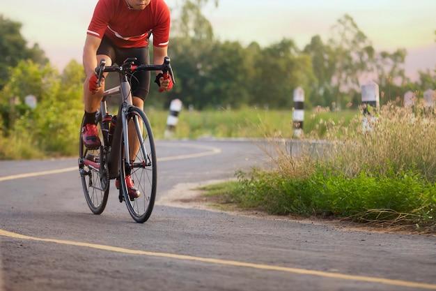 Cycliste sur une route en plein air au coucher du soleil Photo Premium