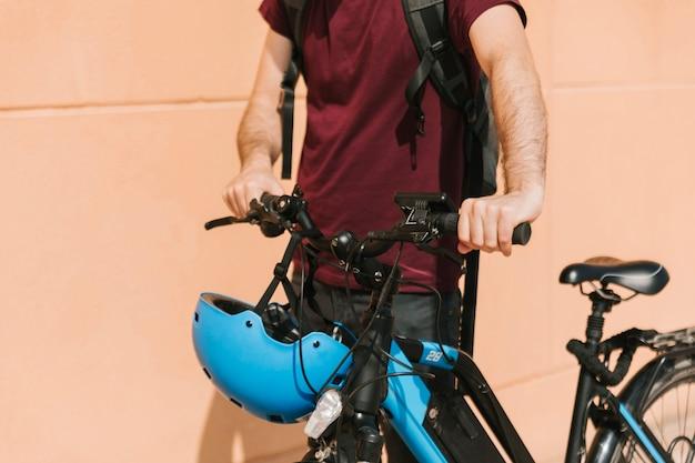 Cycliste urbain marchant à côté du vélo électrique Photo gratuit