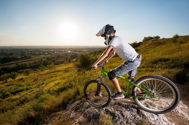 Cycliste en vtt sur la colline sous le ciel bleu Photo Premium