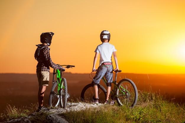 Les cyclistes avec des vélos de montagne sur la colline dans la soirée Photo Premium