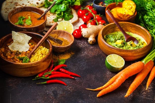 Dal, palak paneer, curry, riz, chapati, chutney dans des bols en bois sur une table sombre. Photo Premium