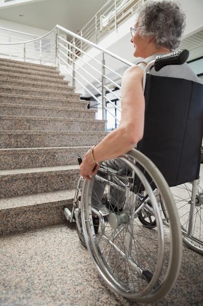 Une dame âgée en fauteuil roulant levant les yeux Photo Premium