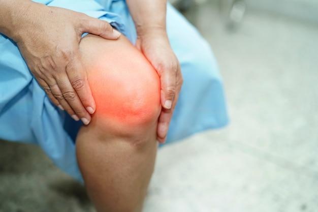 Dame asiatique d'âge moyen patiente touche et ressent la douleur à son genou: concept médical en bonne santé. Photo Premium