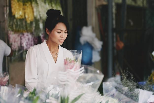 Dame asiatique bien habillée, choisissant le bouquet dans le magasin de fleurs Photo gratuit