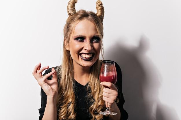 Dame Attrayante Souriante En Costume De Vampire Appréciant La Fête. Photo De Fille Qui Rit Avec Du Faux Sang Dans Un Verre à Vin. Photo gratuit