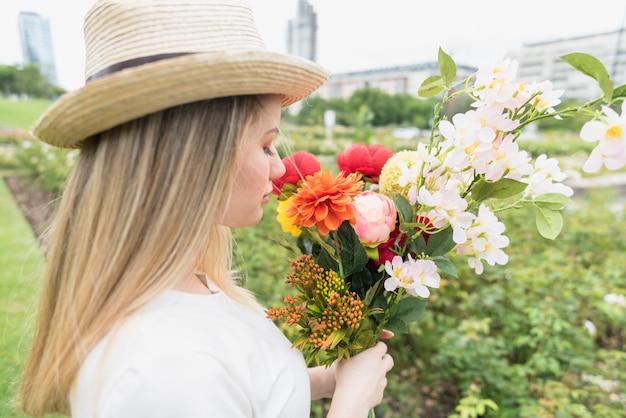 Dame au chapeau avec bouquet de fleurs dans le parc de la ville Photo gratuit