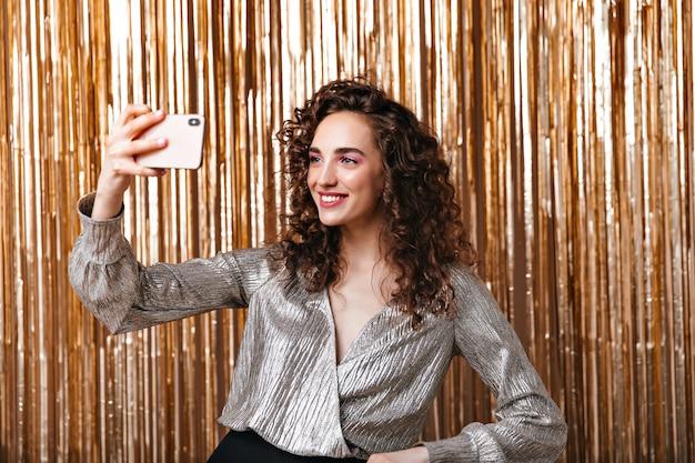 Dame Aux Cheveux Noirs En Chemisier Argenté Prenant Selfie Sur Fond D'or Photo gratuit