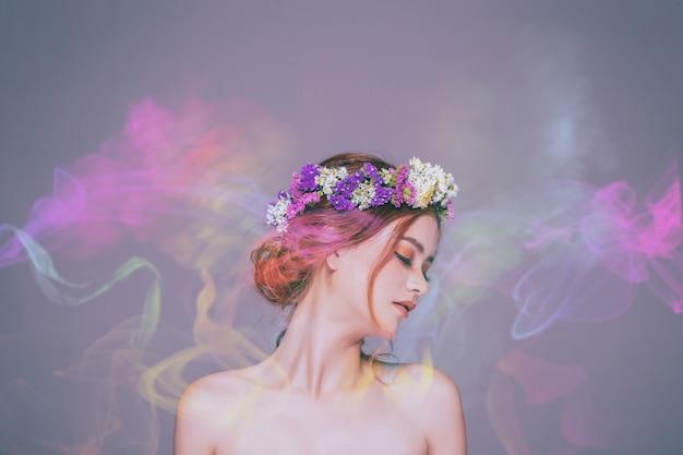 La dame aux fleurs est métisse, caucasienne et asiatique. elle est fascinée par l'odeur du parfum coloré. Photo Premium