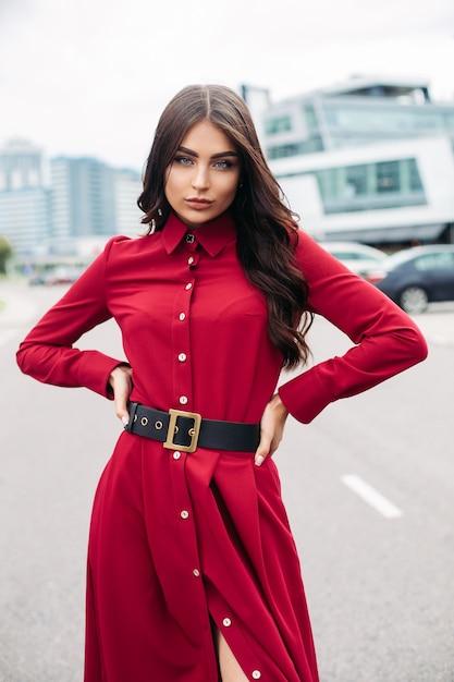 Dame élégante Confiante En Robe Rouge Posant à La Caméra Tout En Se Tenant La Main à La Taille. Mode Féminine Photo gratuit