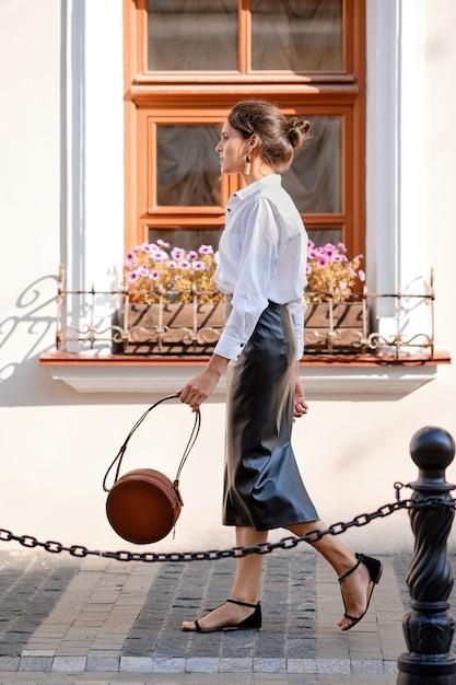 Dame élégante en jupe en cuir et chemise blanche marchant dans la rue avec un sac à main en cuir Photo Premium