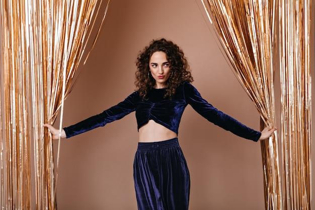 Dame élégante En Tenue De Velours Bleu Foncé Posant Sur Fond D'or Photo gratuit