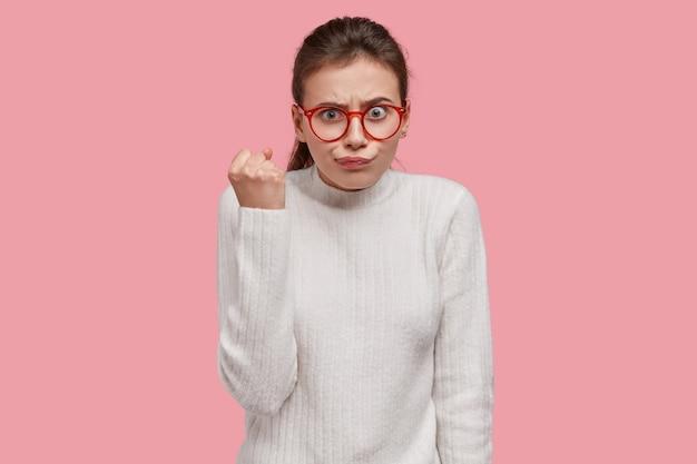 Dame Européenne Stricte Avec Un Look Agréable, Montre Son Poing, Porte Des Lunettes Optiques Et Un Pull Blanc, Démontre Son Aversion Photo gratuit