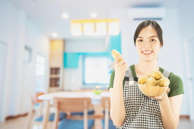 Dame heureuse tenant des trucs de cuisine sur fond d'espace copie Photo gratuit