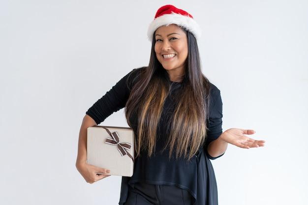 Dame joyeuse avec cadeau de noël présentant des nouvelles Photo gratuit