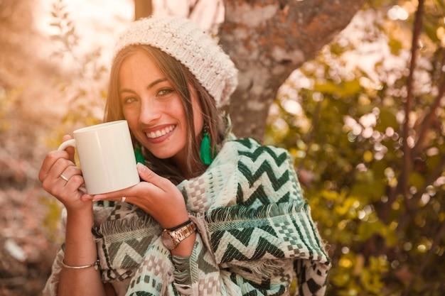 Dame joyeuse avec une tasse en forêt Photo gratuit