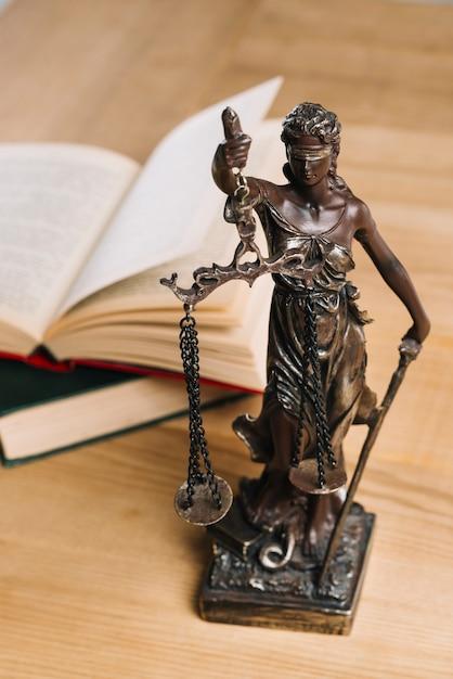 Dame De La Justice Et Des Livres De Droit Sur Une Table En Bois Photo gratuit