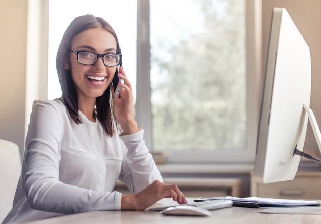 Dame à lunettes parle au téléphone. Photo Premium
