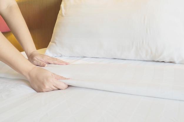 Dame mains mis en place un drap blanc dans la chambre d'hôtel Photo gratuit