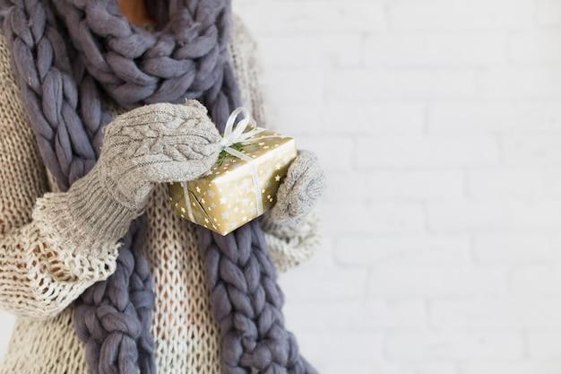 Dame en mitaines et écharpe avec coffret en mains Photo gratuit
