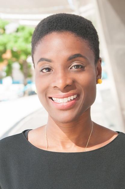 Dame noire positive posant à l'extérieur et souriant Photo gratuit