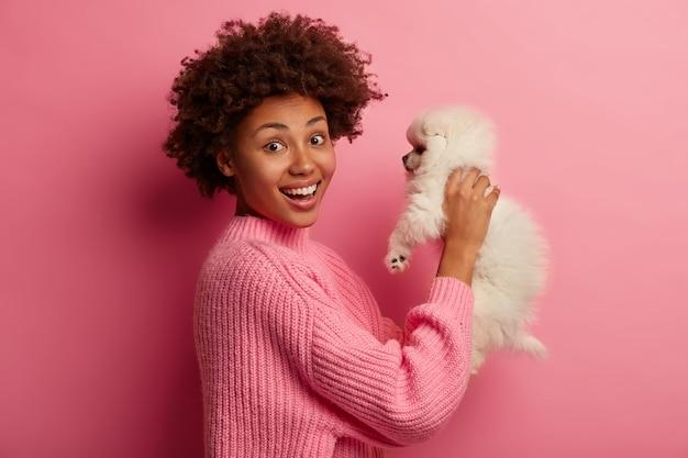 Dame à La Peau Foncée Garde Les Lèvres Arrondies, Veut Embrasser Un Animal Adorable, Joue Avec Un Petit Chiot Photo gratuit
