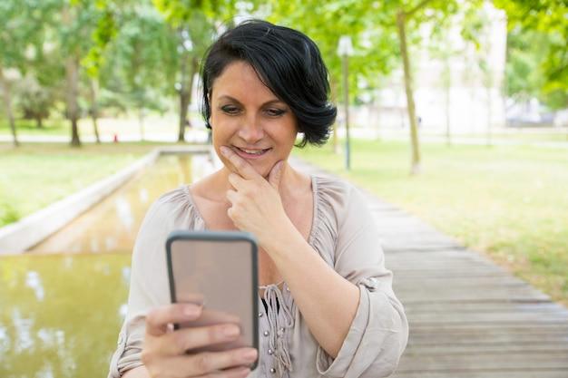 Dame pensive souriante prenant des photos sur smartphone Photo gratuit