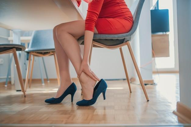 Dame portant des chaussures à talons hauts de longue date se sentir mal à la cheville mal à l'aise Photo Premium