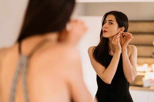 Dame Porte Une Belle Robe Noire En Regardant Dans Le Miroir Photo gratuit