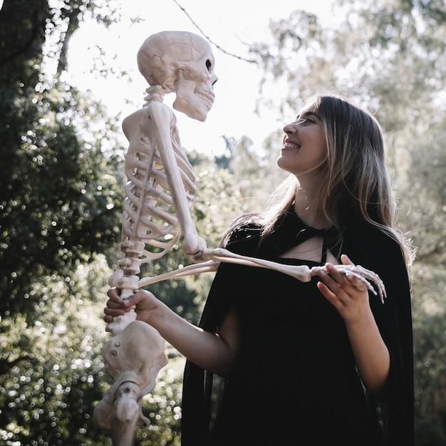 Dame Riante En Tenue De Sorcière Tenant Un Squelette Photo gratuit