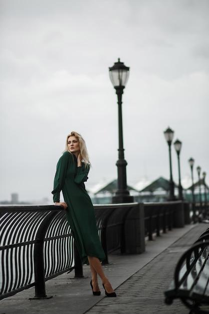Dame en robe verte pose sur le remblai dans un jour brumeux Photo gratuit