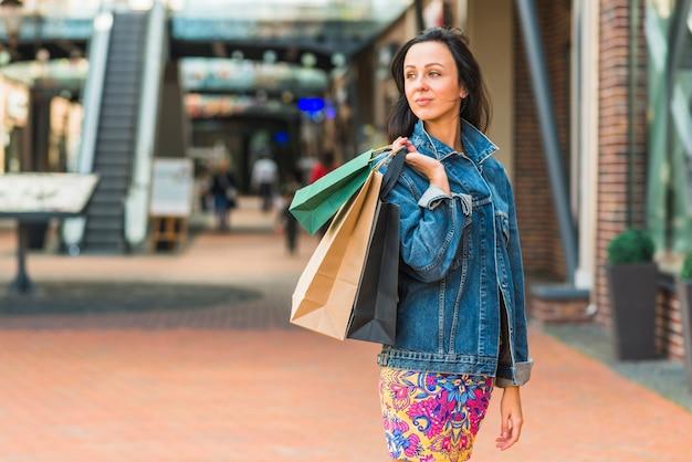 Dame avec des sacs dans un centre commercial Photo gratuit