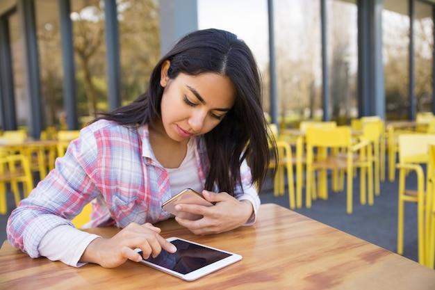 Dame sérieuse à l'aide de tablette et smartphone au café en plein air Photo gratuit