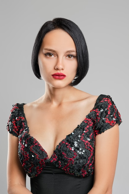Dame sérieuse aux cheveux noirs courts et aux lèvres rouges qui pose en studio Photo Premium