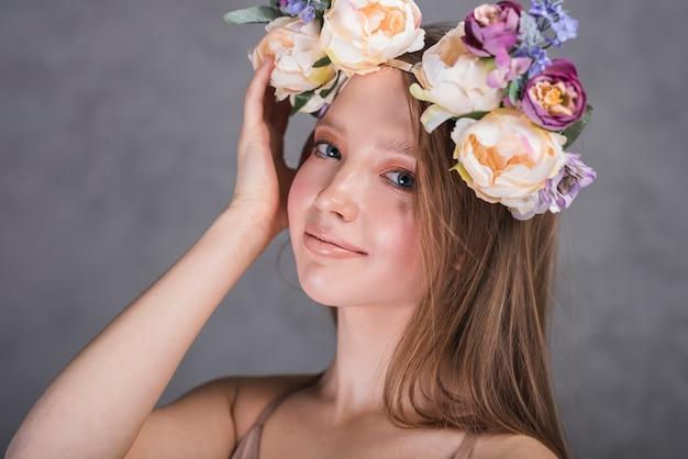 Dame souriante avec des fleurs sur la tête Photo gratuit