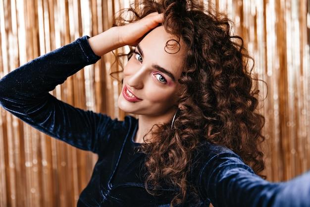 Dame Touche Ses Cheveux Bouclés Et Prend Selfie Sur Fond D'or Photo gratuit