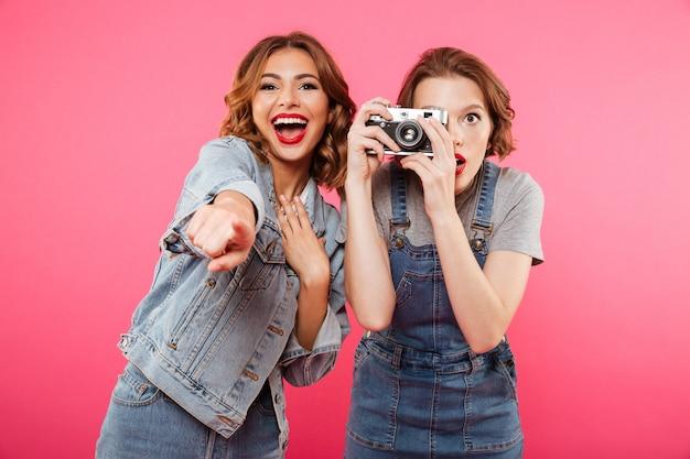 Des Dames Heureuses Font Des Photos Par Caméra Et Pointent Vers Vous. Photo gratuit