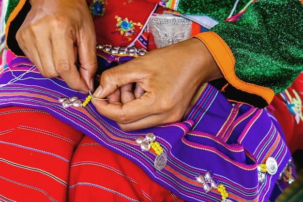 Des dames de la tribu de thailander hill montrent des travaux de couture et de décoration de costumes pour les touristes dans son village. Photo Premium