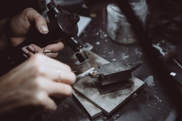 Dans l'atelier, une bijoutière est en train de souder des bijoux Photo gratuit