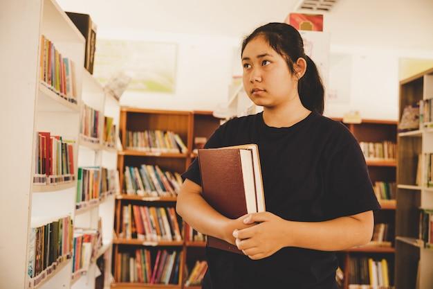 Dans la bibliothèque - jeune étudiante avec des livres dans une bibliothèque de lycée. Photo gratuit