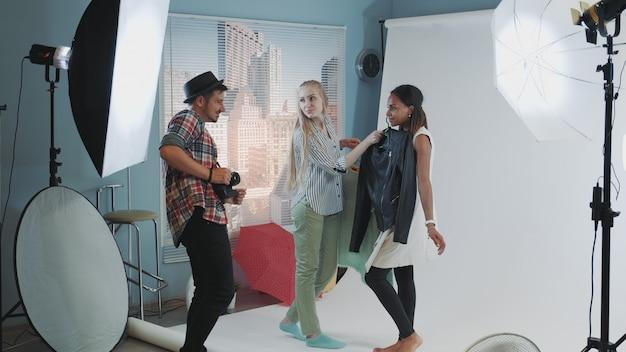 Dans Les Coulisses De La Séance Photo: Un Photographe Avec Une Assistante Choisit Des Vêtements Pour La Séance Photo Du Mannequin Photo Premium