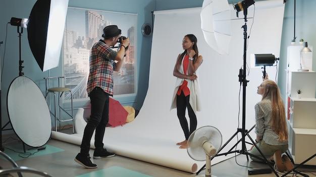 Dans Les Coulisses De La Séance Photo En Studio Moderne: Assistant Ajustant Le Projecteur Sur La Séance Photo Photo Premium