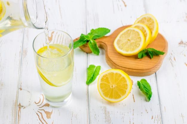 Dans un gobelet en verre, une limonade froide est versée sur un fond en bois blanc entouré de citrons. Photo Premium