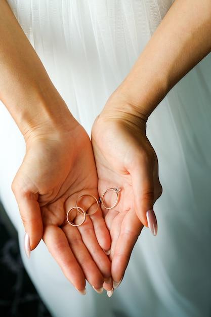 Dans les paumes des alliances de la jeune fille ou de la mariée. Photo Premium