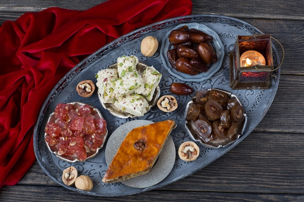 Dans une plaque d'argent dattes, noix, halva, délice turc, baklava et une lanterne Photo Premium