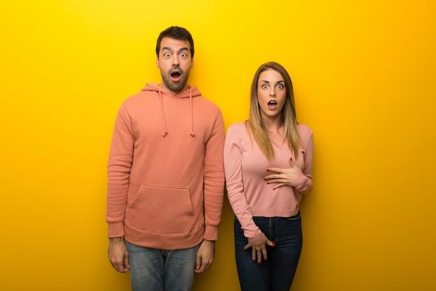 Dans la saint valentin groupe de deux personnes sur fond jaune avec expression faciale surprise et choquée Photo Premium