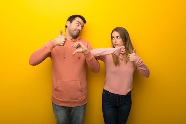 Dans la saint valentin groupe de deux personnes sur fond jaune faisant bon signe. indécis entre oui ou non Photo Premium