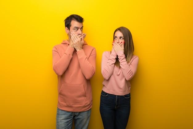 Dans la saint valentin groupe de deux personnes sur fond jaune se couvrant la bouche avec les mains pour avoir dit quelque chose d'inapproprié Photo Premium